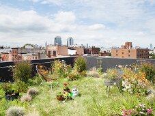 Begrüntes Dach mit Blumen und Stühlen und Blick auf Brooklyn und Manhattan