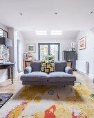 Grey sofa on colourful rug