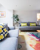 Grey sofas paired with colourful rug and scatter cushions in living room