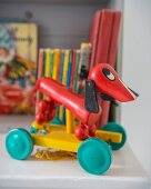 Red retro pull-along dachshund in front of colourful children's books