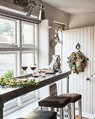 Wine glasses and dog ornaments on narrow table next to window next to open front door decorated with wreath
