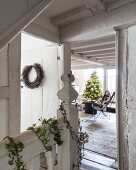 Vintage stairwell decorated with ivy and wreath and view of Christmas tree in living area