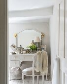 Festively decorated mirror and feminine accessories on white dressing table