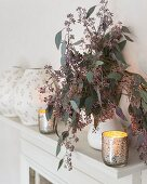 White mantelpiece decorated with candlelight and twigs
