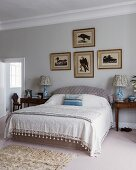 Pictures of birds above bed in classic bedroom