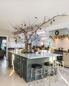 Festively decorated branches in vase on kitchen island with bar stools