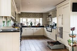 Large, white, modern, country-house kitchen with black worksurface