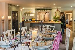 Table set for Christmas dinner in front of island counter in country-house kitchen