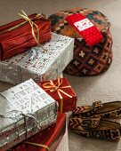 Arrangement of wrapped presents, tapestry slippers and kilim pouffe