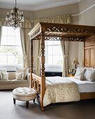 Ornate four-poster bed with scatter cushions in bedroom with bay window and buttoned-tufted stool