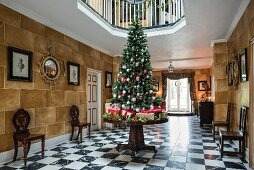 Christmas tree and presents on table in large reception hall