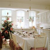 Festively set table and Christmas tree in country-house kitchen