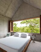 Wood and concrete bedroom with view of countryside through panoramic window