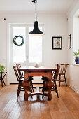 Holztisch mit massiven Beinen und alte Stühle im hellen Esszimmer