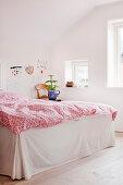 Rot-weiße Bettwäsche auf dem Bett mit Husse im weißen Schlafzimmer