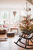 Schaukelstuhl vor geschmücktem Weihnachtsbaum im Wohnzimmer
