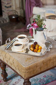 Cups of coffee, coffee pot and pastries on upholstered footstool