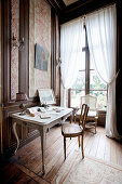 Baroque chair at old desk against classic panelled wall