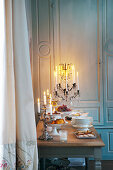 Buffet on candlelit table in front of panelled wall
