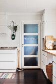 Besen und Schaufel neben Tür mit Glaseinsatz in weißer Küche