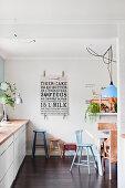 Bunte Hocker in weißer Küche mit dunkler Dielenboden