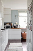 White fitted kitchen with window and dark wooden floor