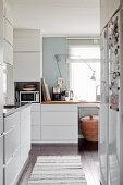 weiße Einbauküche mit Fenster und dunklem Dielenboden