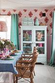 Gedeckter Esstisch vor einer Vitrine und rosafarbener Wand