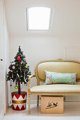 Weihnachtsbaum im bunten Eimer und Barocksofa unterm Dachfenster