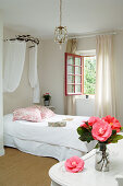Vase of camellias in French-style bedroom