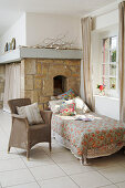 Armchair and couch in front of window and exposed stone wall