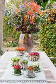 Small cake-shaped arrangements of natural materials as autumnal table decorations