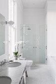 Bad ganz in Weiß mit hoher Decke und Dusche in der Nische