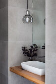 Countertop basin on wooden plate, pendant lamp in wall niche above in gray-tiled guest toilet