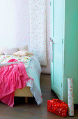 Floral bedlinen on bed, floral wallpaper and mint-green wardrobe
