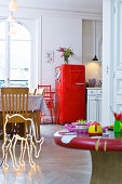 Red fridge and neon deer silhouette in kitchen of period apartment
