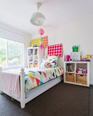 Wooden bed with colorful bedding in girl's room with white walls