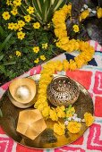 Golden tealight holders and flower garland on metal tray