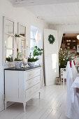 Weihnachtlich dekorierte Kommode unter Sprossenfenstern mit Spiegeln