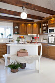 Bench next to island in country-house kitchen