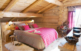 Gingham blanket on bed in rustic bedroom of log cabin