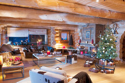 Christmas tree and arrangements of candles in living room of log cabin