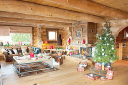Christmas tree and fire in fireplace in log cabin