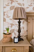Table lamp, sprouting hyacinth in paper bag and candle on bedside table