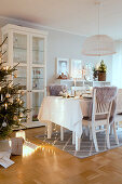 Christmas tree next to set table with cosy lighting