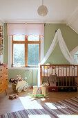 Gitterbett mit Baldachin im nostalgischen Kinderzimmer mit grüner Wand