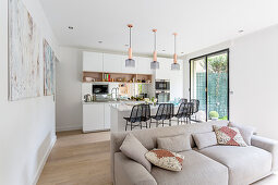 Grey sofa in front of open-plan kitchen with barstools at island counter