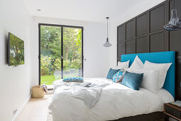 Bed against black panelled wall in front of floor-to-ceiling window with garden view