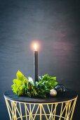 Brennende schwarze Kerze mit DIY-Blätterkranz