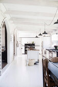 Open, white kitchen with vintage furnishings in a former church